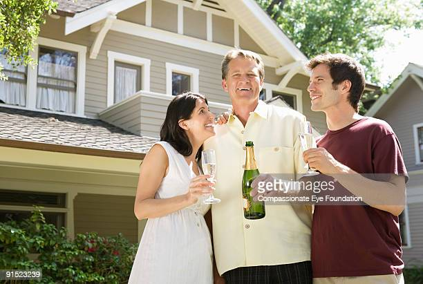two men and woman smiling and holding champagne