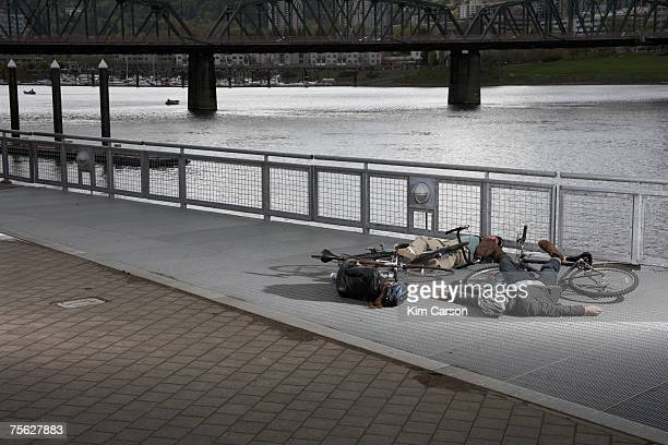 two men and woman with bicycles lying on pavement by river after collision - dead bodies in car accident photos stock photos and pictures
