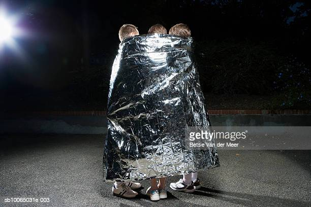 Two men and women wrapped in silver survival blanket