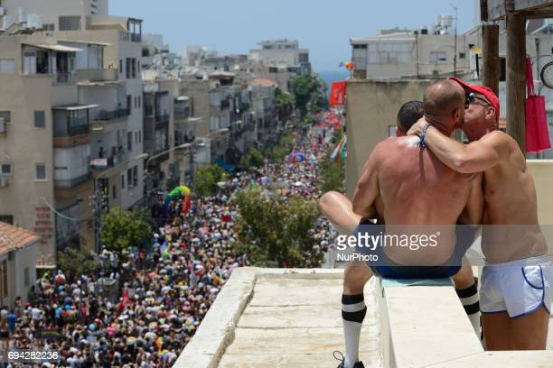 Two men are kissing while watching from a roof ar the annual gay pride parade in Tel Aviv June 09 2017 About 200000 members of the Israeli and...
