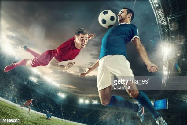 twee mannen zijn te voetballen en ze concurreren met elkaar - teamsport stockfoto's en -beelden