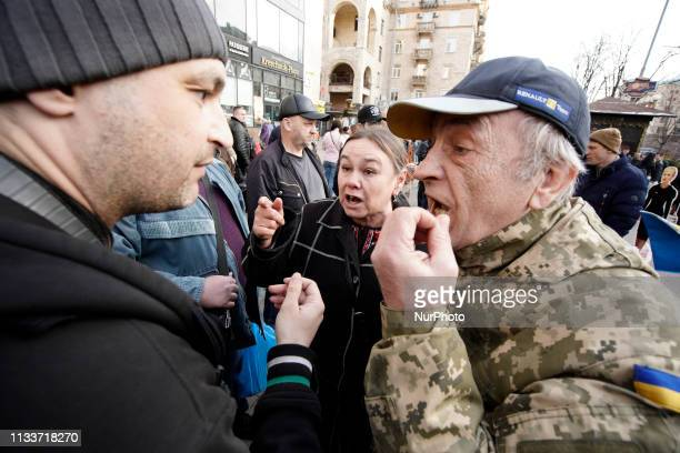 Two men are seen arguing near an exhibit with cutout figures of presidential candidates including a figure of Russian president Vladimir Putin in...