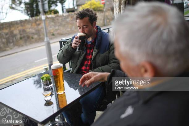 Two men are seen drinking beer on April 26, 2021 in St Andrews, United Kingdom. Hospitality and non-essential shops have reopened from today under...