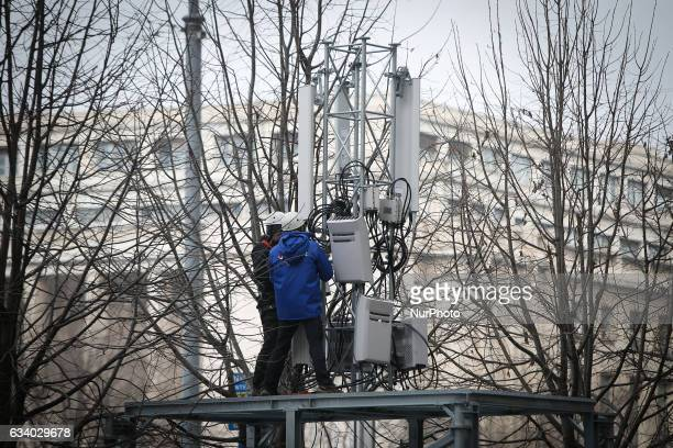 Two men are seen installing mobile communications equipment on a parking lot near government headquarters on 6 February 2017 Previously only one...