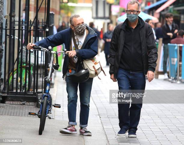 Two men are seen wearing facemasks, one walking along his bike in Chinatown. Public people are seen wearing facemasks while out shopping in London...