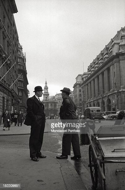 Two men are talking on the pavement of the London Strand in front of the back of St MaryleStrand church in the City of Westminster London 1957