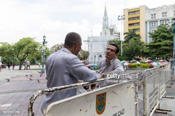Two men are talking with each other on the street in downtow, in the background a church can be seen in Cali, Colombia.