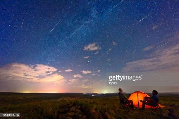 Two men are watching the Perseid meteor shower, on the edge of the tent.