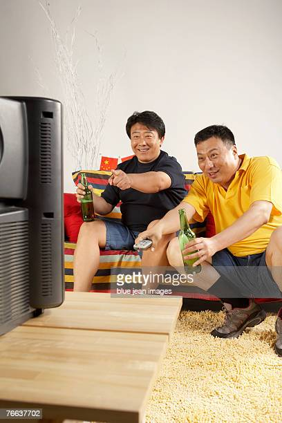 Two men are watching TV and drinking beer.