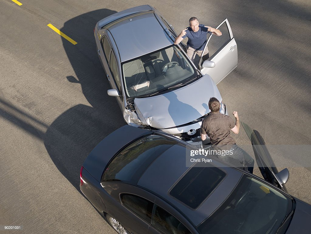 Two men arguing about damage in car collision : Stock Photo