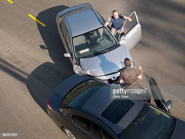 two men arguing about damage in car collision - crash stock pictures, royalty-free photos & images