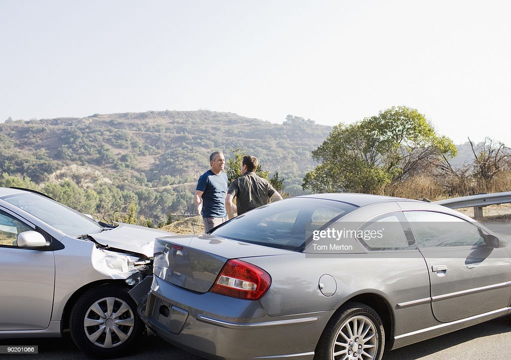 Two men arguing about damaged cars : Stock Photo