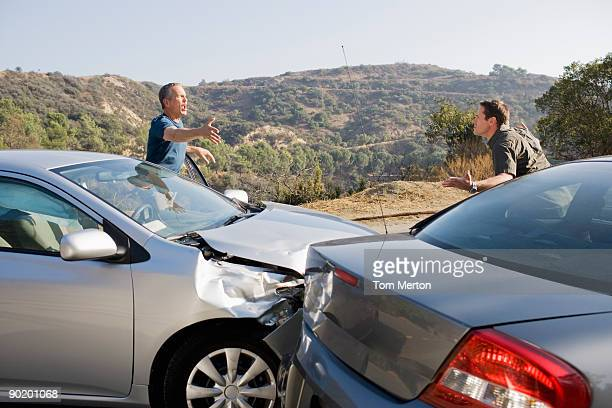 Dos hombres discutiendo sobre dañado automóviles
