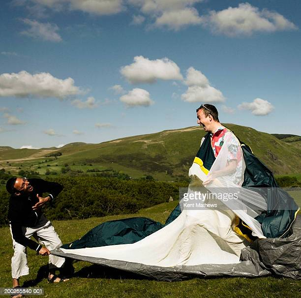 Two men assembling tent outdoors, laughing