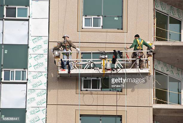 two men at a new construction site on scaffolding - construction platform stock photos and pictures