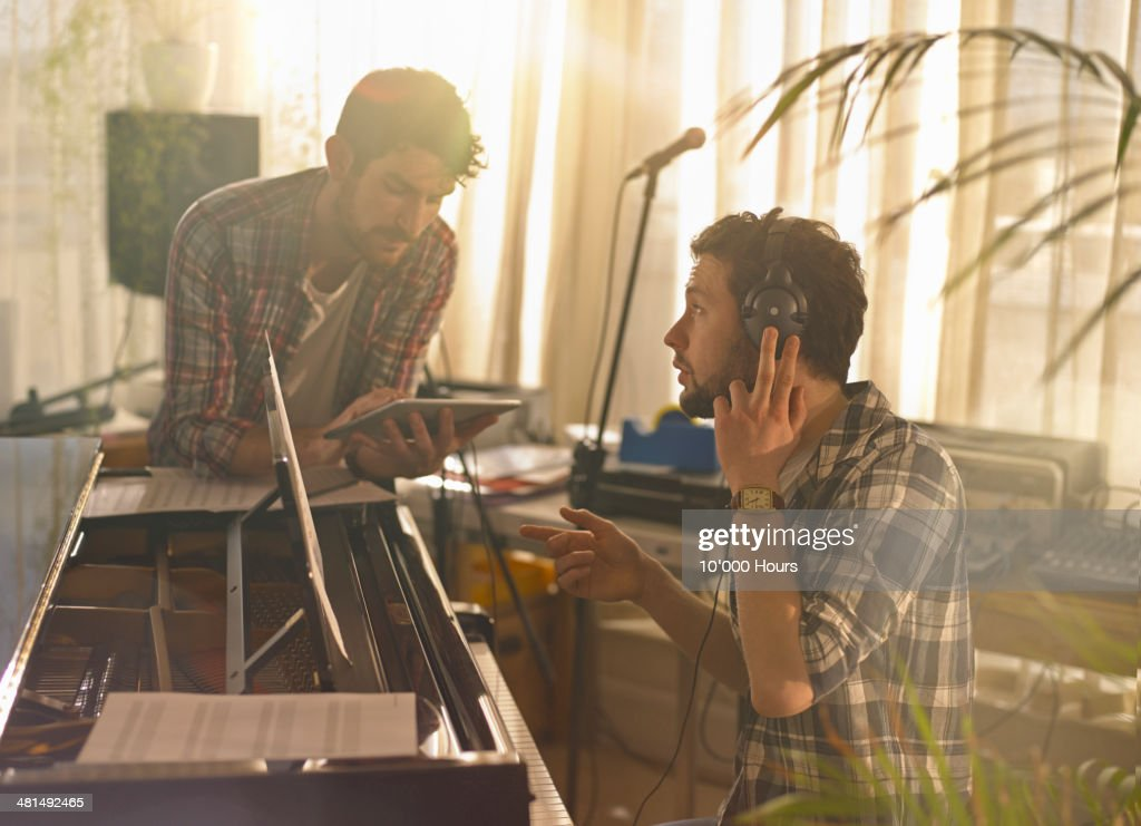 Two men at a piano using an iPad : Stock Photo