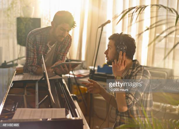 Two men at a piano using an iPad