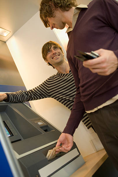 Two men at an ATM machine.