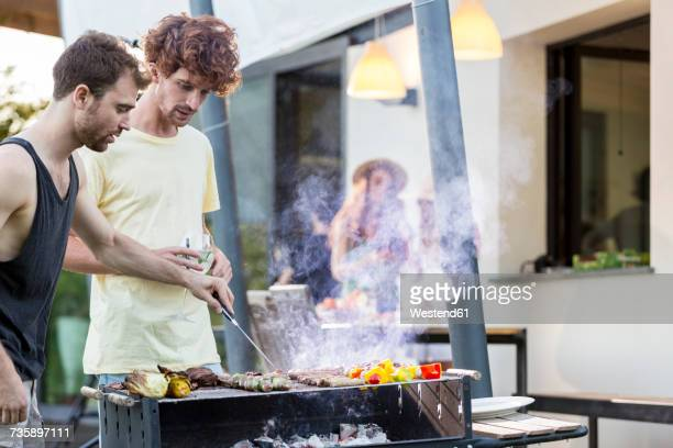 Two men at barbecue grill