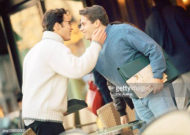 two men at cafe terrace, smiling, side view - mock turtleneck stock pictures, royalty-free photos & images