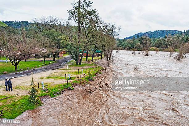 two men at coloma campground watch american river high waters - california flood stock photos and pictures