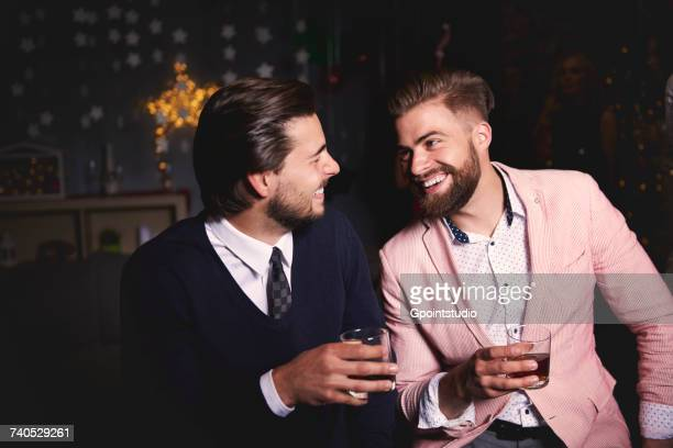 Two men at party, holding drinks, laughing