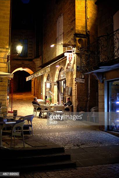 two men at street cafe on cobblestone street - sarlat stock photos and pictures