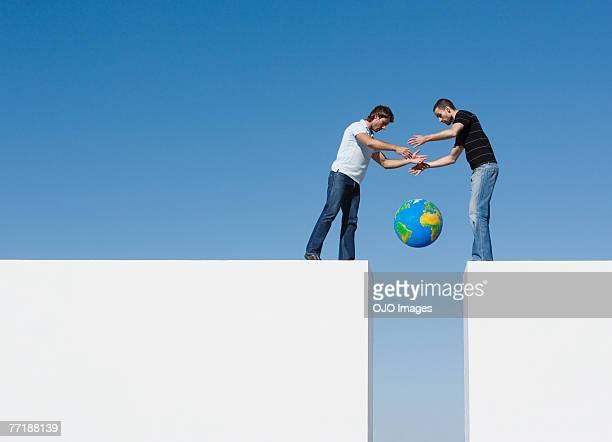 Zwei Männer auf einer Mauer laden eine Welt