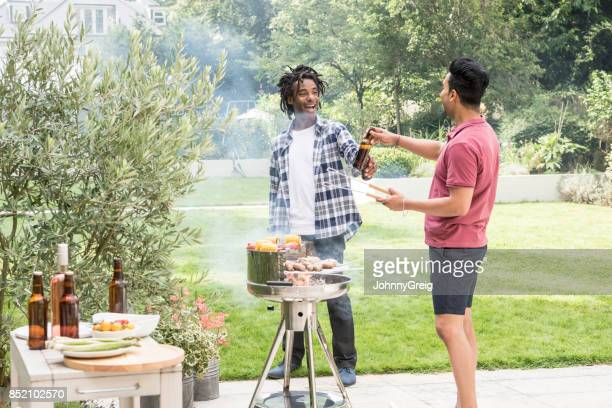 Two men barbecuing food and drinking beer