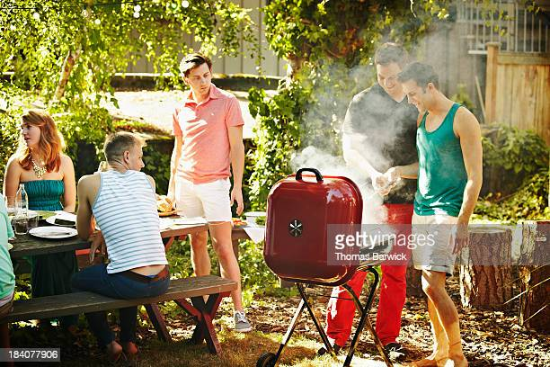 Two men barbecuing together in backyard