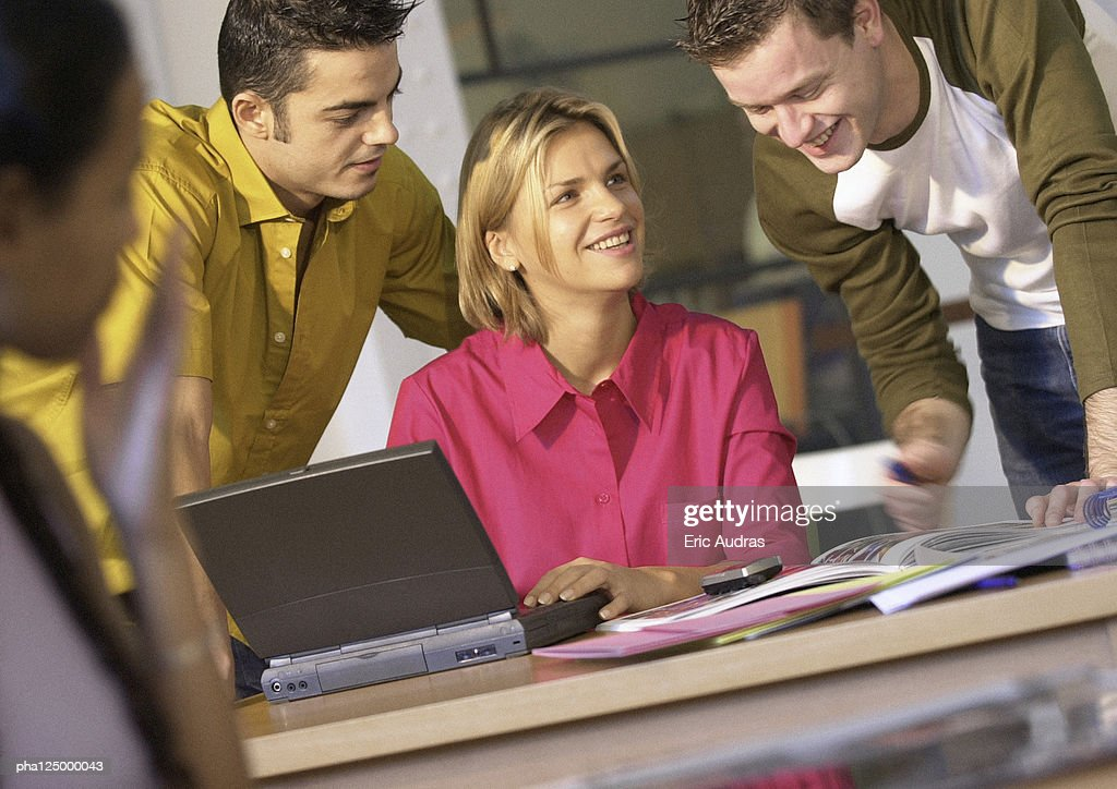 Two men behind woman using laptop computer : Stock Photo