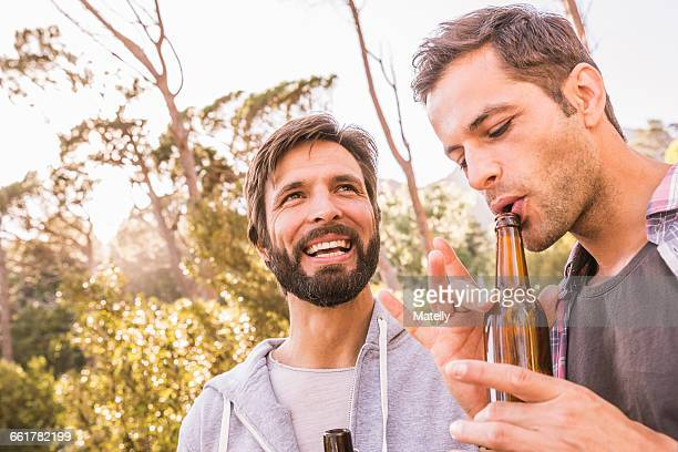 Two men blowing into beer bottle whilst camping in forest, Deer Park, Cape Town, South Africa