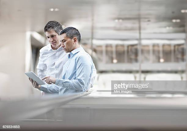 Two men, business colleagues, looking at a digital tablet screen.
