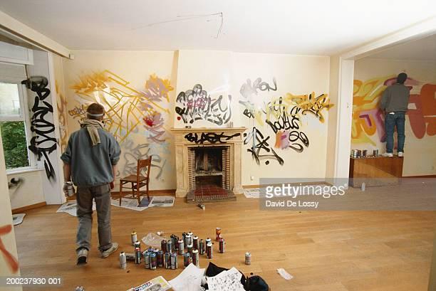 two men busy in spray painting, rear view - grafite produção artística - fotografias e filmes do acervo