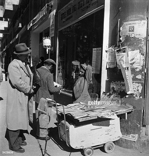 Two men buying newspapers from a street stand in Tel Aviv Israel