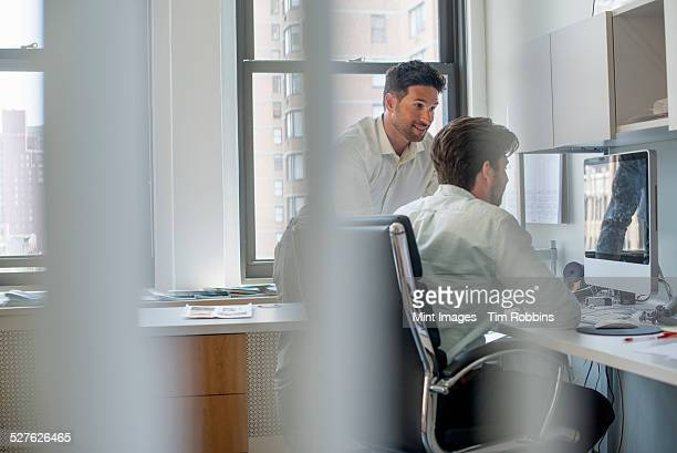 Two men by a computer screen, talking and planning.