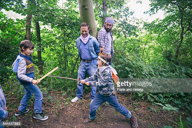 Two men captured whilst boys have sword fight in forest