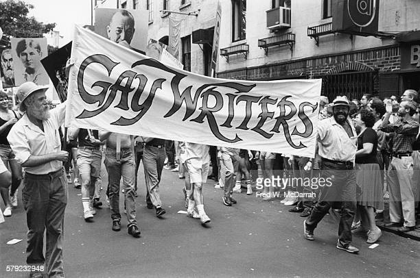 Two men carry a banner that reads 'Gay Writers' during the annual Gay Pride Day March as it passes in front of the old Stonewall Inn New York New...