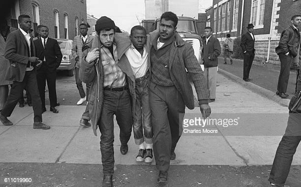 Two men carry a boy injured during an anti-segregation demonstration, Selma, Alabama, 1965.