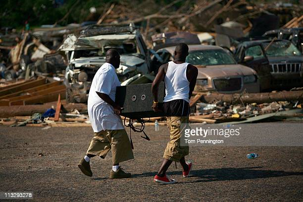 Two men carry a large car stereo speaker through a destroyed neighborhood on April 30, 2011 in Tuscaloosa, Alabama. Alabama, the hardest-hit of six...