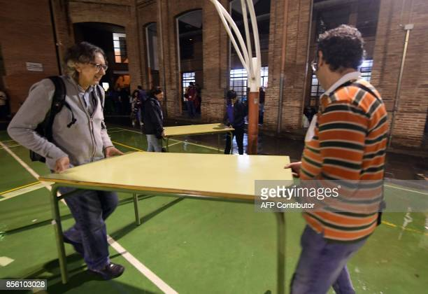 Two men carry a table to set up a polling station in a school of Barcelona on October 1 on the day of a referendum on independence for Catalonia...