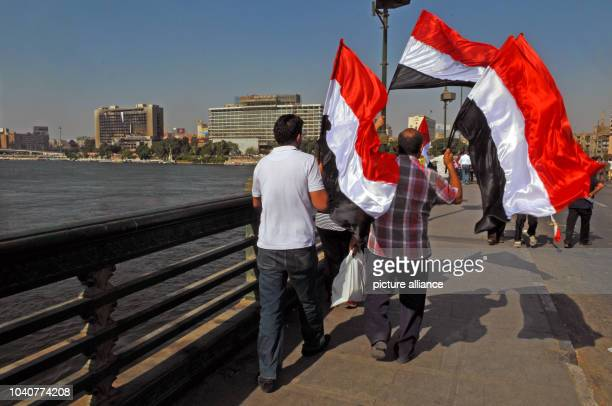 Two men carry flags on their way to a demonstration against Egyptian President Mursi at Tahrir Square in Cairo Egypt 30 June 2013 Egyptian President...