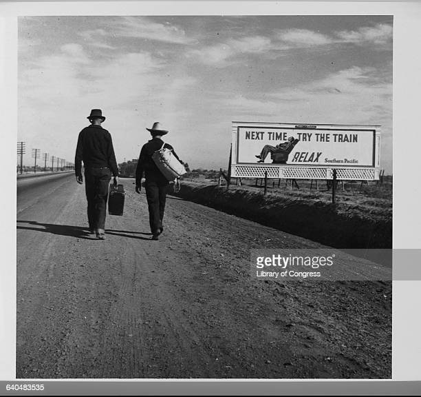 Two men carry suitcases as they walk down a deserted highway towards Los Angeles during the Great Depression A billboard next to the highway reads...