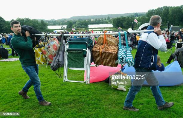 Two men carry their picnic equipment as they attend the annual Castle Howard Proms Spectacular concert held on the grounds of the Castle Howard...