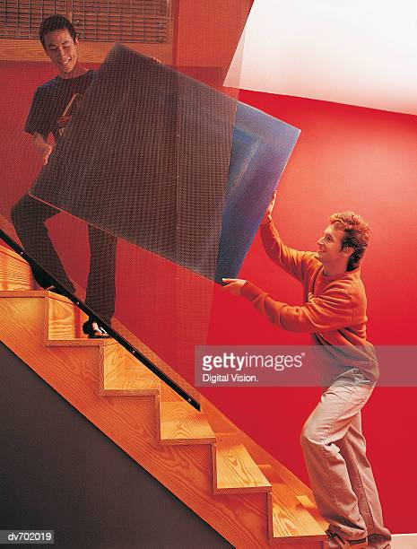 Two Men Carrying a Painting up some Stairs