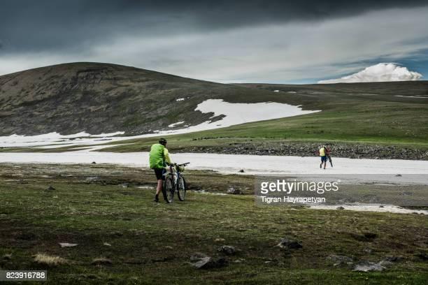 Two men carrying bikes up the impassable snowed terrain, Armenian highland, Caucasus