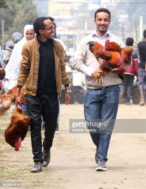 Two men carrying chickens walk at the Sholla bazaar ahead of Easter celebrations in Addis Ababa Ethiopia on April 07 2018 Orthodox Christians fast...