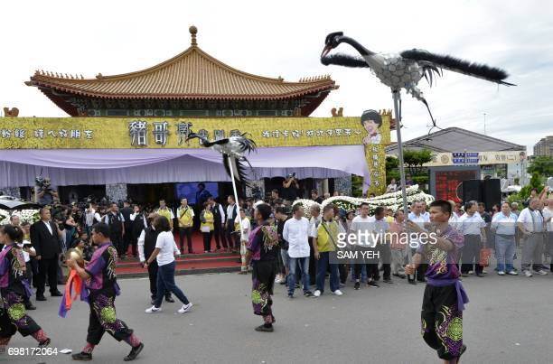 Two men carrying craneshaped effigies perform outside a funeral hall during a ceremony for late Taiwanese celebrity Chu Keliang at a local funeral...