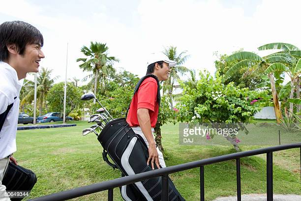 two men carrying golf bag - 北マリアナ諸島 ストックフォトと画像