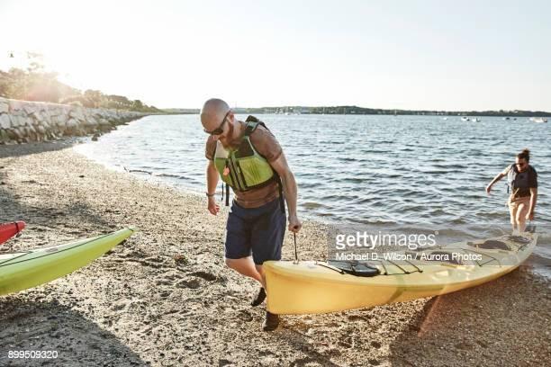 Two men carrying kayak on lakeshore, Portland, Maine, USA